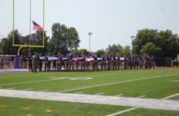 Tech ROTC students begin stretching out a large flag over Tech's football field.