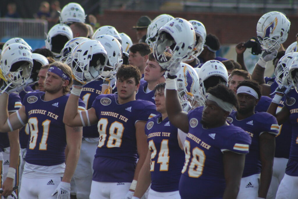 Tech football players hold their helmets in the air prior to kickoff.