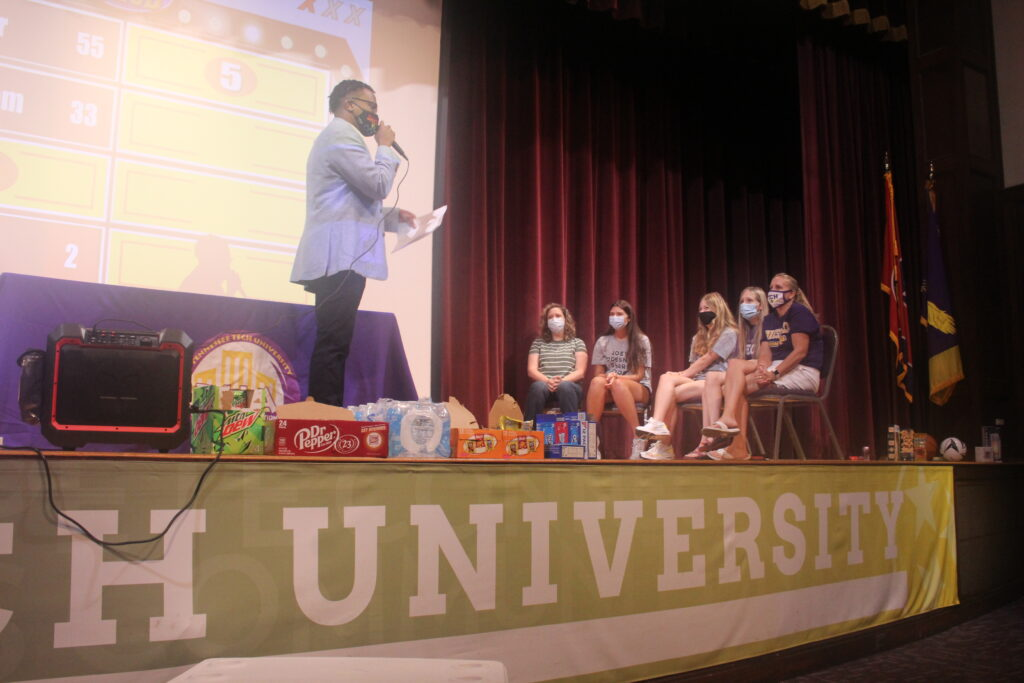 Students sit on a stage and answer questions from Black host.